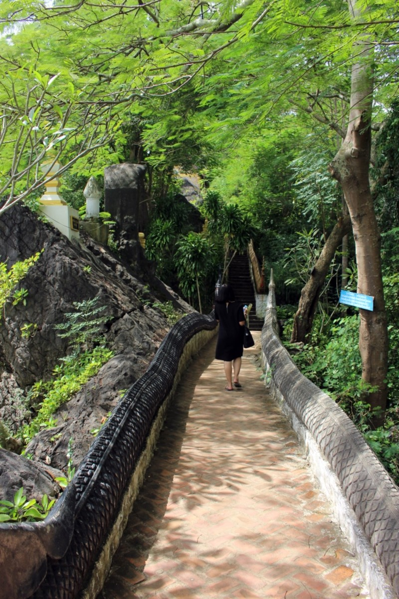Female tourist walks on the path up Mount Phou Si, Luang Prabang, Laos.