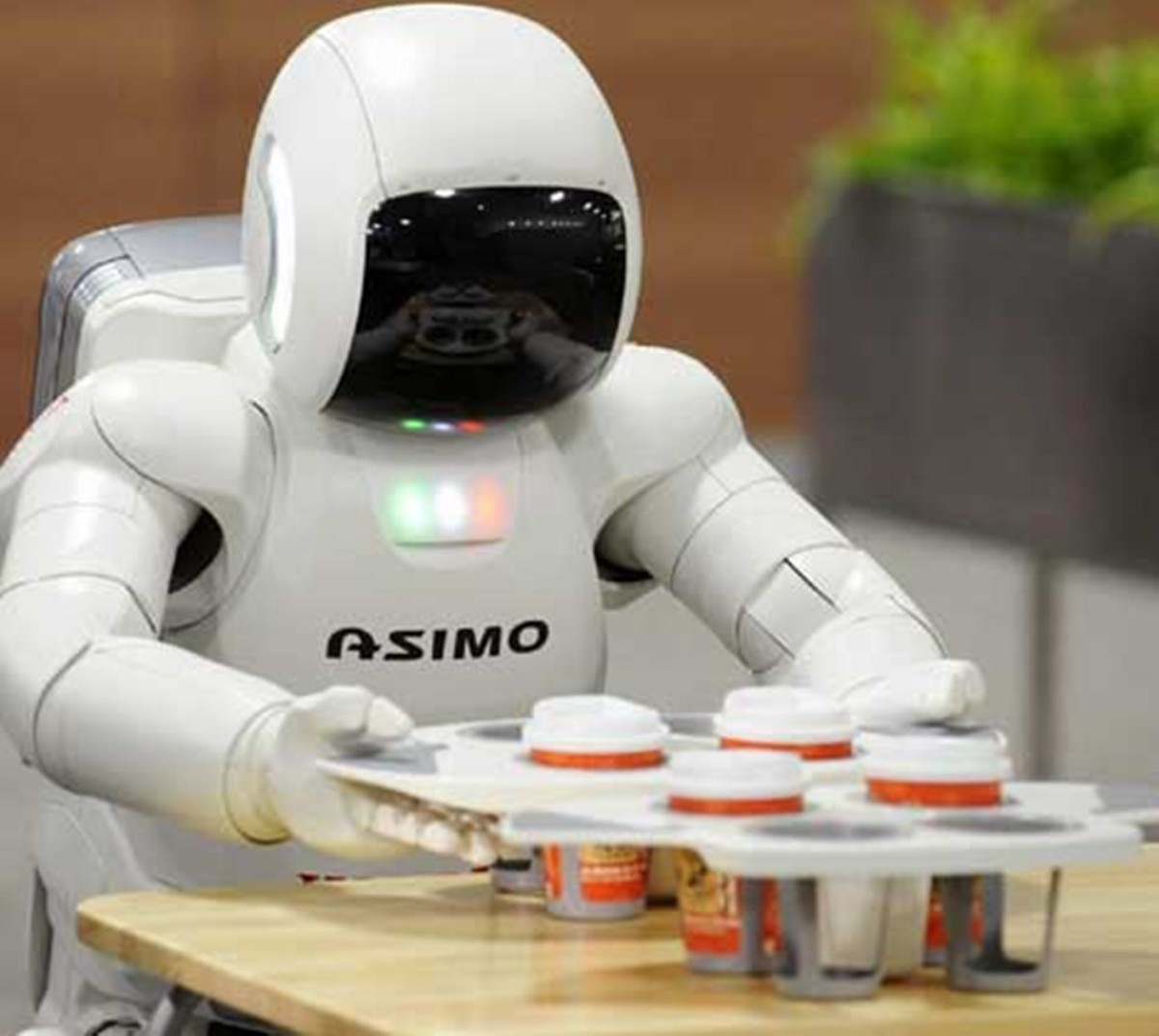 a robot picking up a tray of coffees