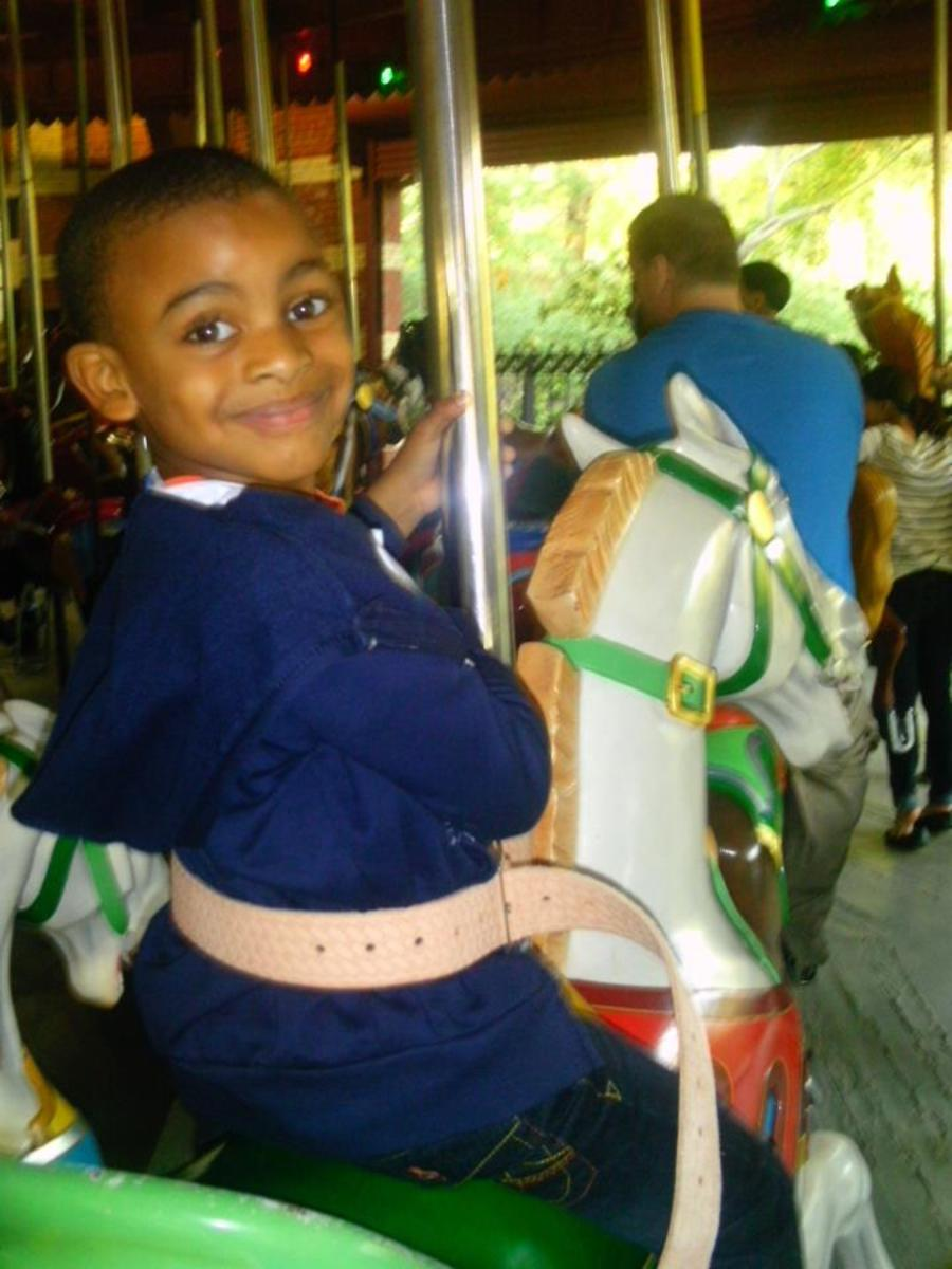 The picture of childhood- gleefully riding  the Central Park carousel while gazing into a camera.