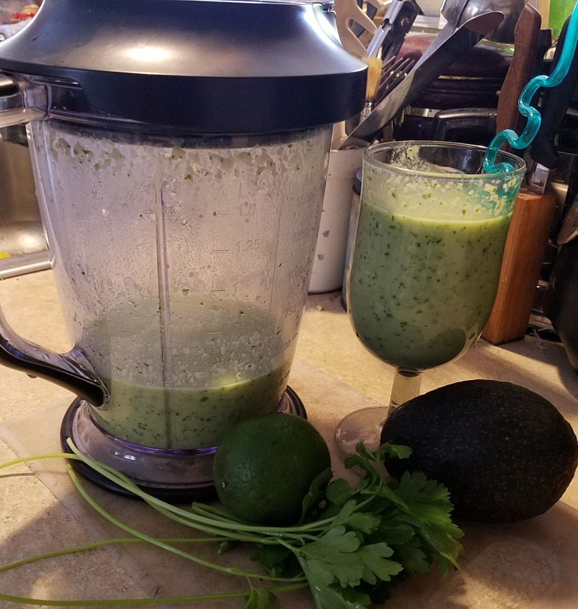 A glass full of this refreshing green smoothie, accompanied by some of the ingredients and the Ninja used to make it.