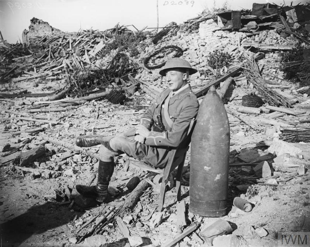Necessity is the mother of invention for a British officer who leans his wrecked chair against an unexploded German shell.