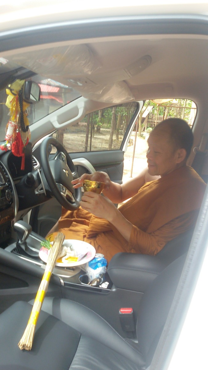 My wife's uncle, a Buddhist monk, is preparing to bless our new vehicle.