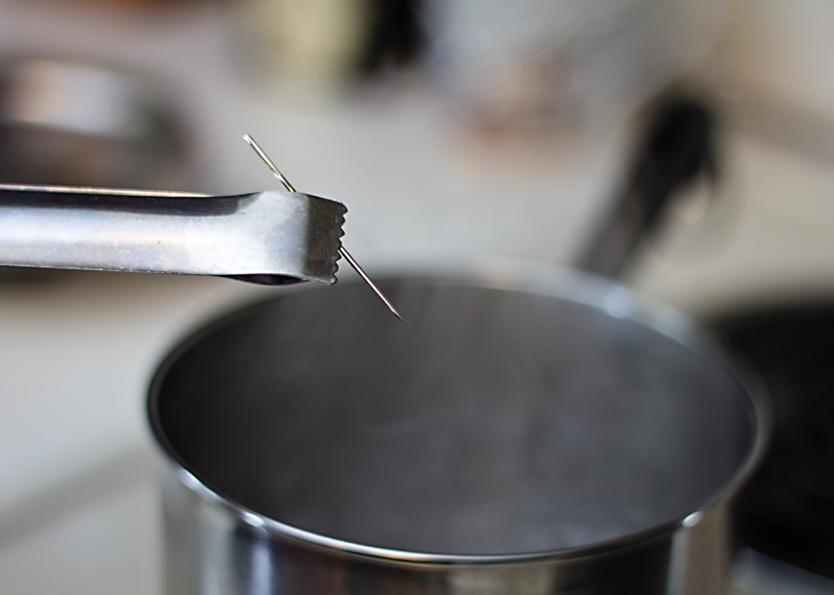 Put the needle in boiling water for at least two minutes.