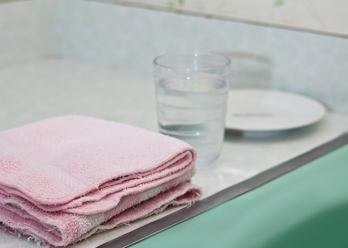 Take your stuff into a thoroughly cleaned bathroom, or use a sink that is easy to bend over and has been well sanitized. Make sure you have some washcloths nearby. Fill one of your glasses with cool water.
