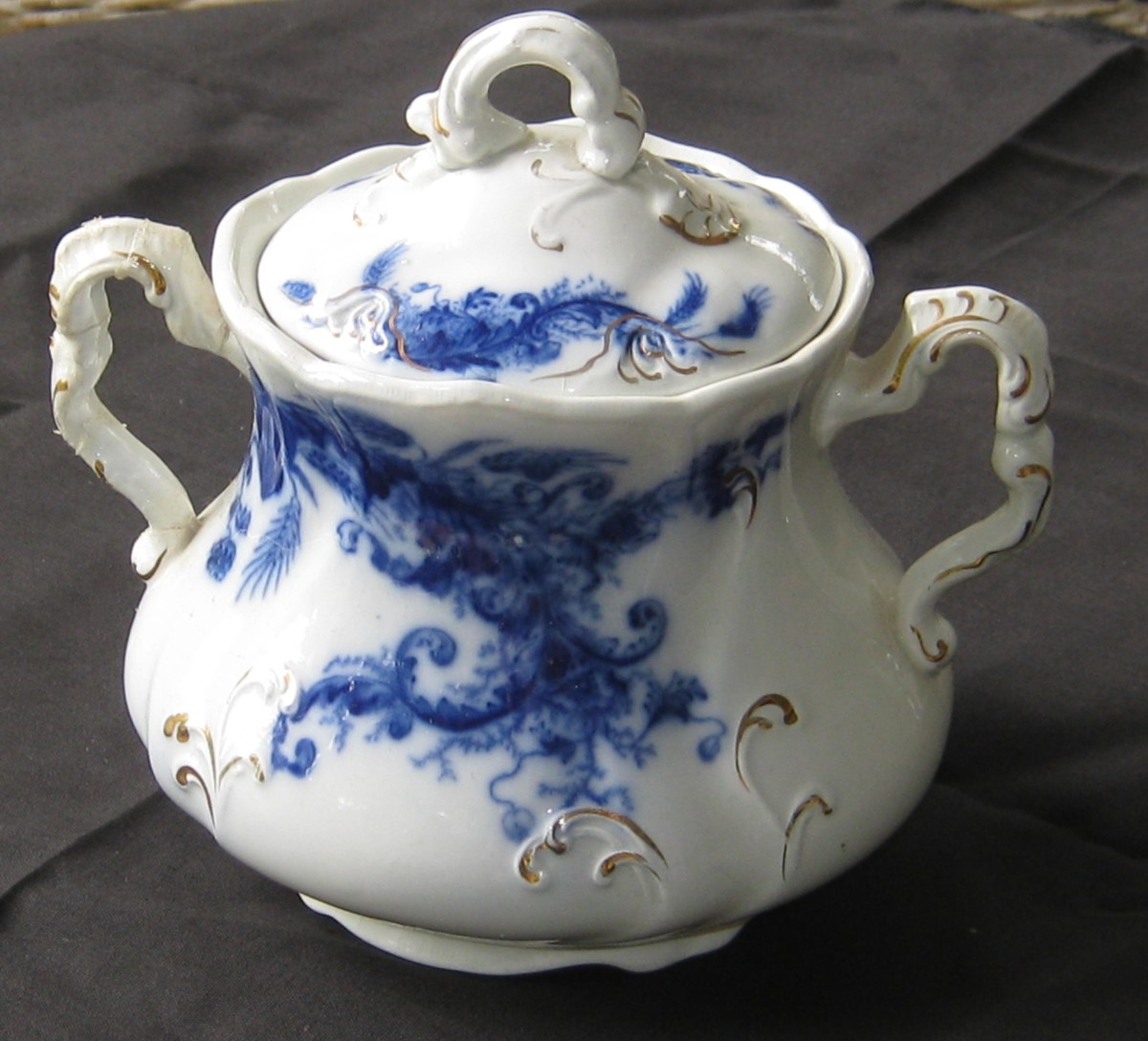 A Flow Blue sugar bowl by Wentworth.  An intact sugar bowl is more valuable than, say, a plate. The sugar bowl has more parts that can break, so the intact handles and lid make this a valuable item.