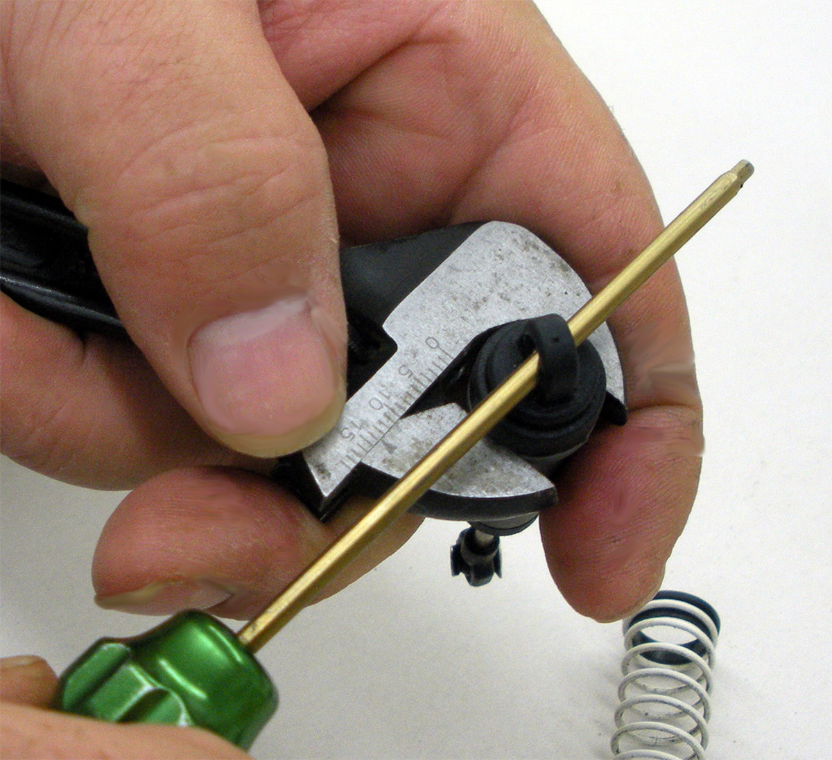 Using screwdriver to turn the cap. Note shock is held upright for this operation.