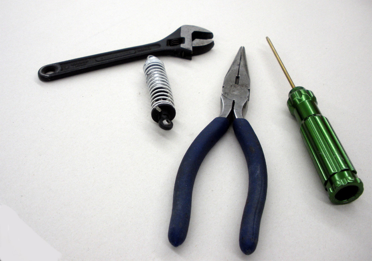 Left to Right: small adjustable wrench; rebuild kit; needle-nose pliers; small screwdriver.