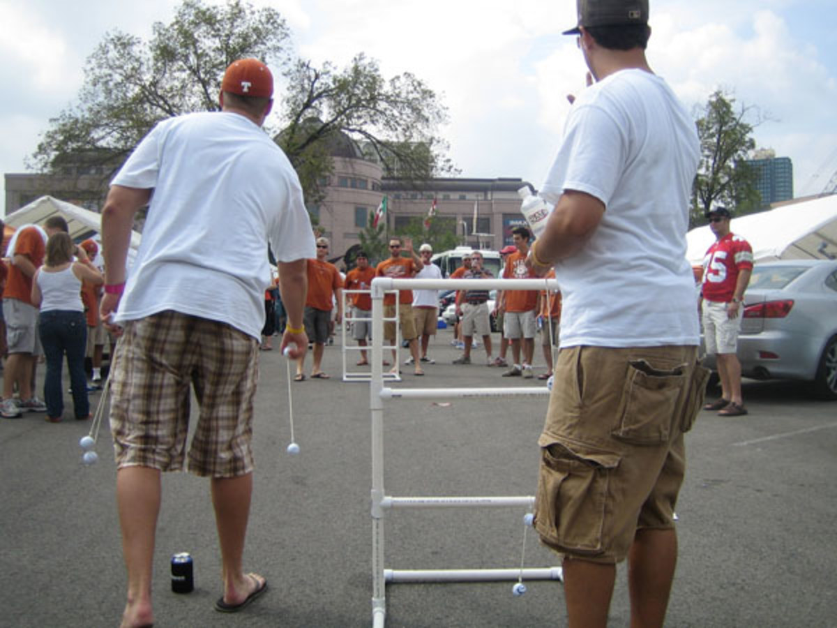 Tailgaters having fun playing ladder toss.