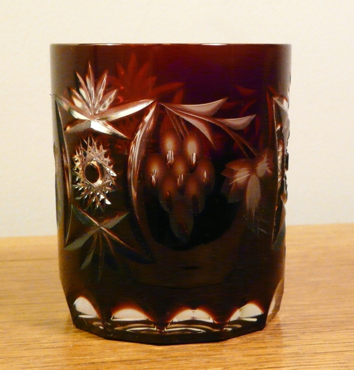 "The pattern at the left is pressed into the glass, but the grapes and leaves at center and right are etched into the stain. It's about 3"" tall."
