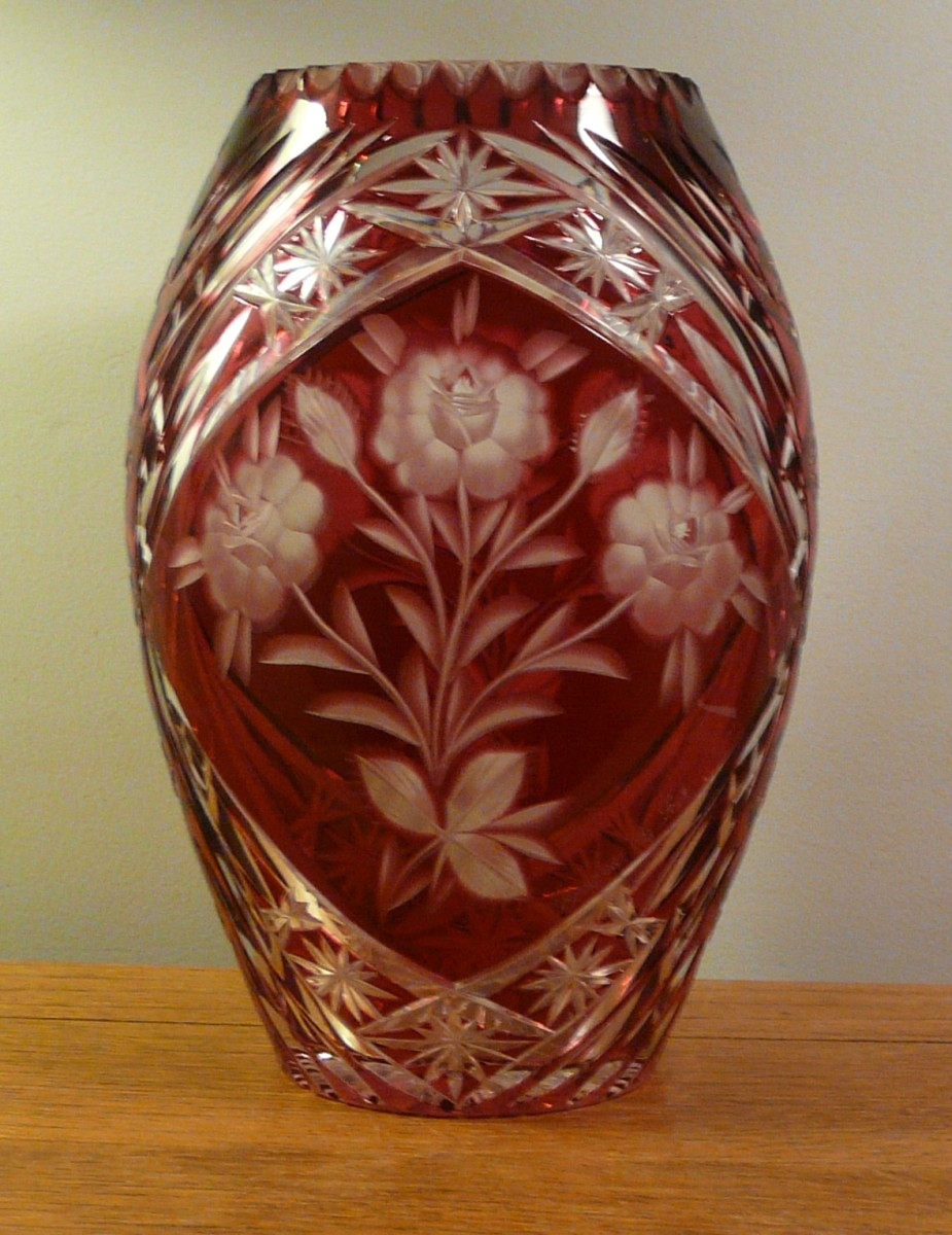 "The flower motif is etched into the red stain, while the bordering pattern is pressed into the glass. The vase is about 12"" tall."
