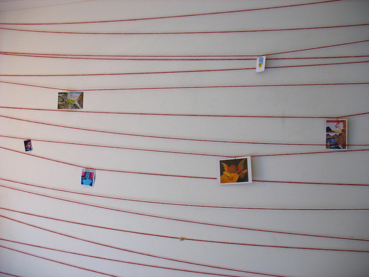 A low cost but effective method. Just criss cross a wall with yarn and attach pictures. From flickr: http://www.flickr.com/photos/orinrobertjohn/139788703