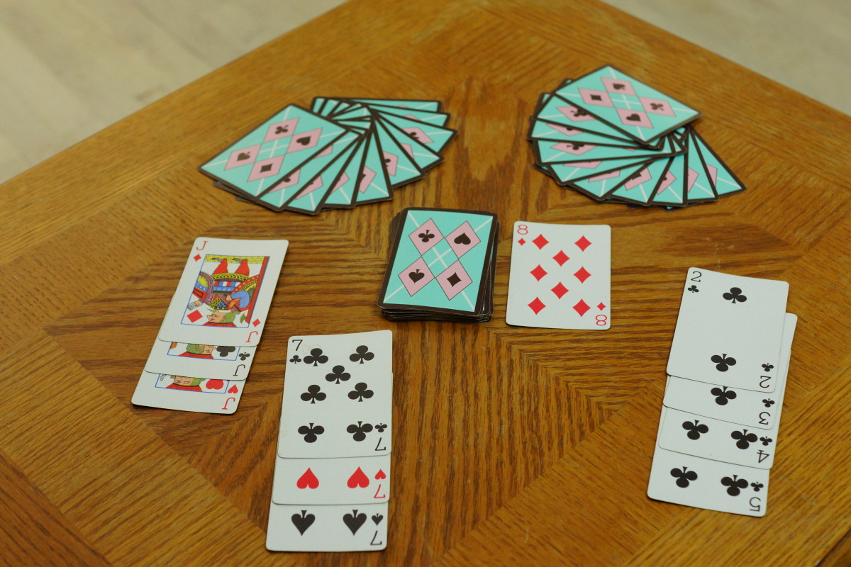 The setup of Rummy next to a few examples of sets and runs