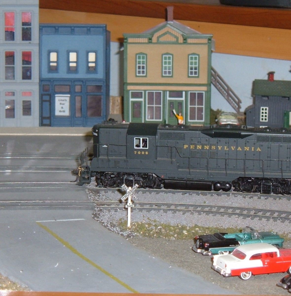 GP9 #7002 slowly passes the grade crossing into town.