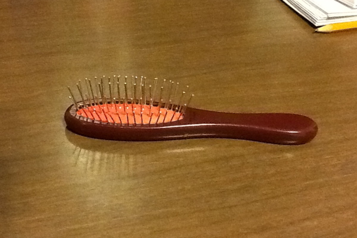 This is an official American Girl doll hairbrush. Note the widely spaced metal bristles that won't snag synthetic hair.