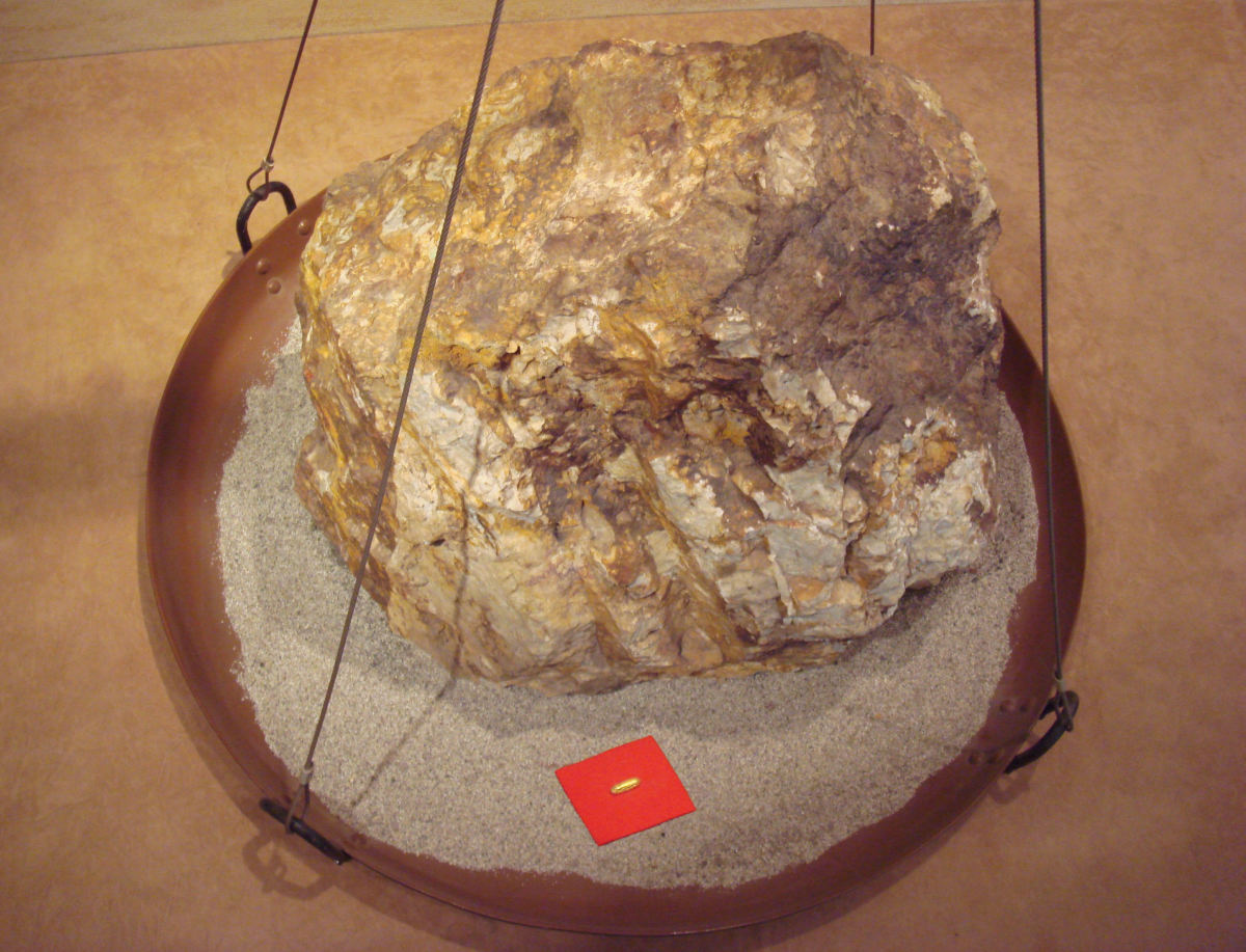 This image shows the relative sizes of an 860 kg block of gold ore, and the 30 g of gold that can be extracted from it.