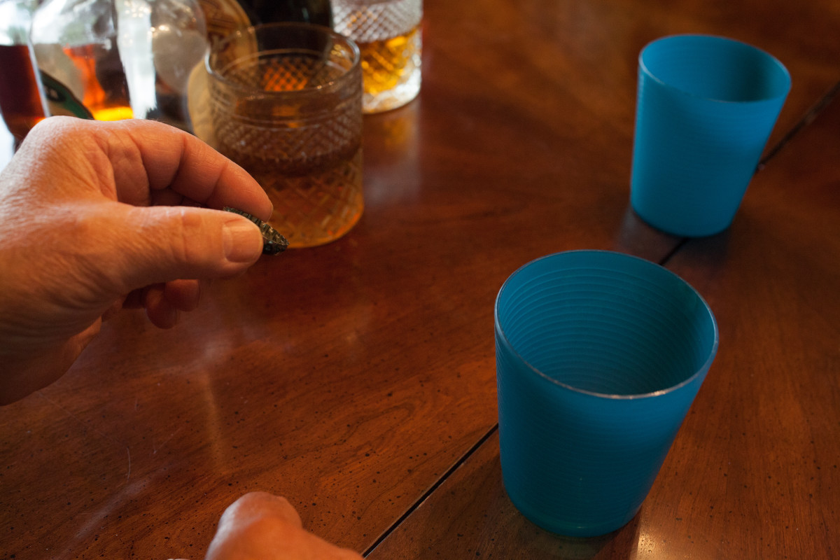 Players face each other and try to throw bottle caps into each others' cups.