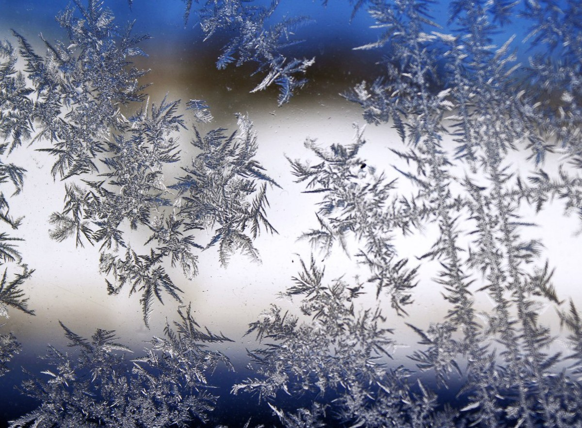 Ice crystals make a pattern on window glass.
