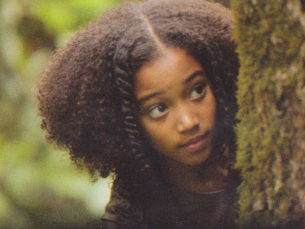 Rue peeks out from behind a tree