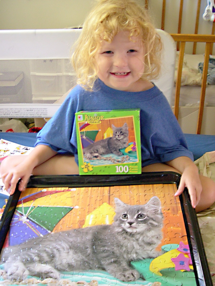 A happy puzzle solver with her framed jigsaw puzzle