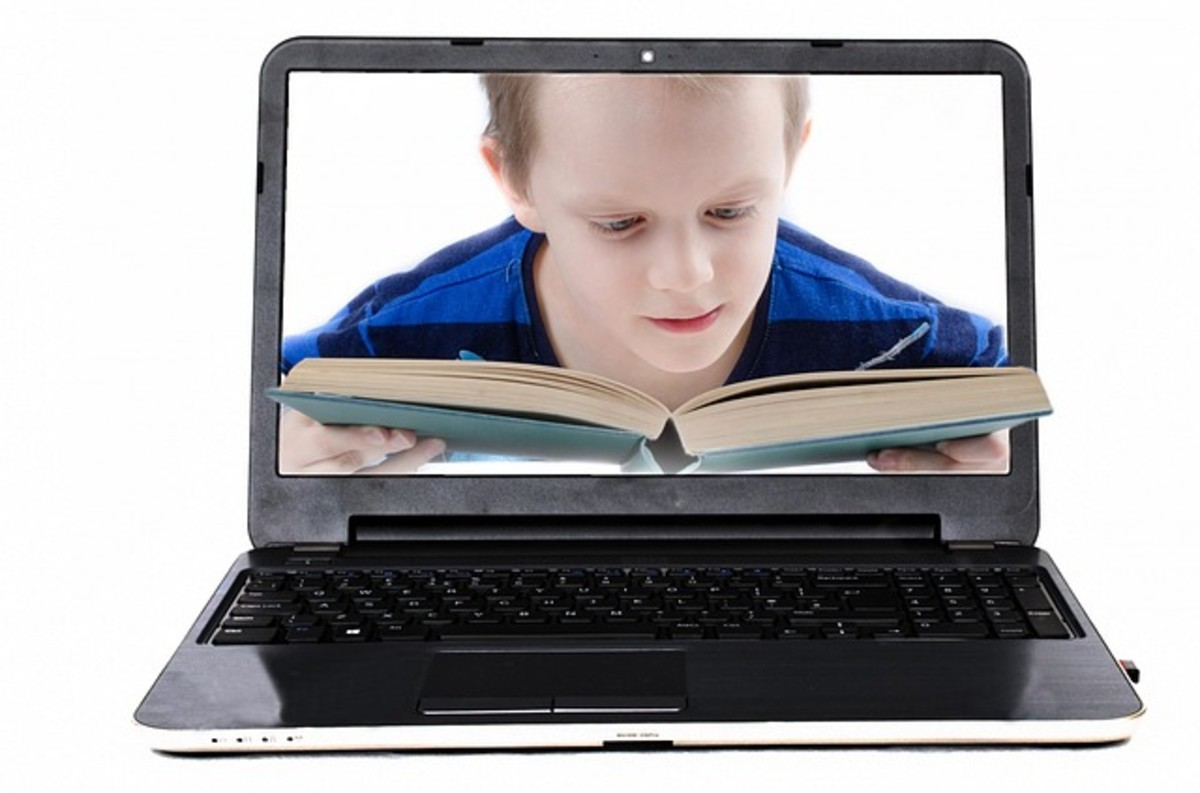A young boy loves reading a book over the use of a laptop.