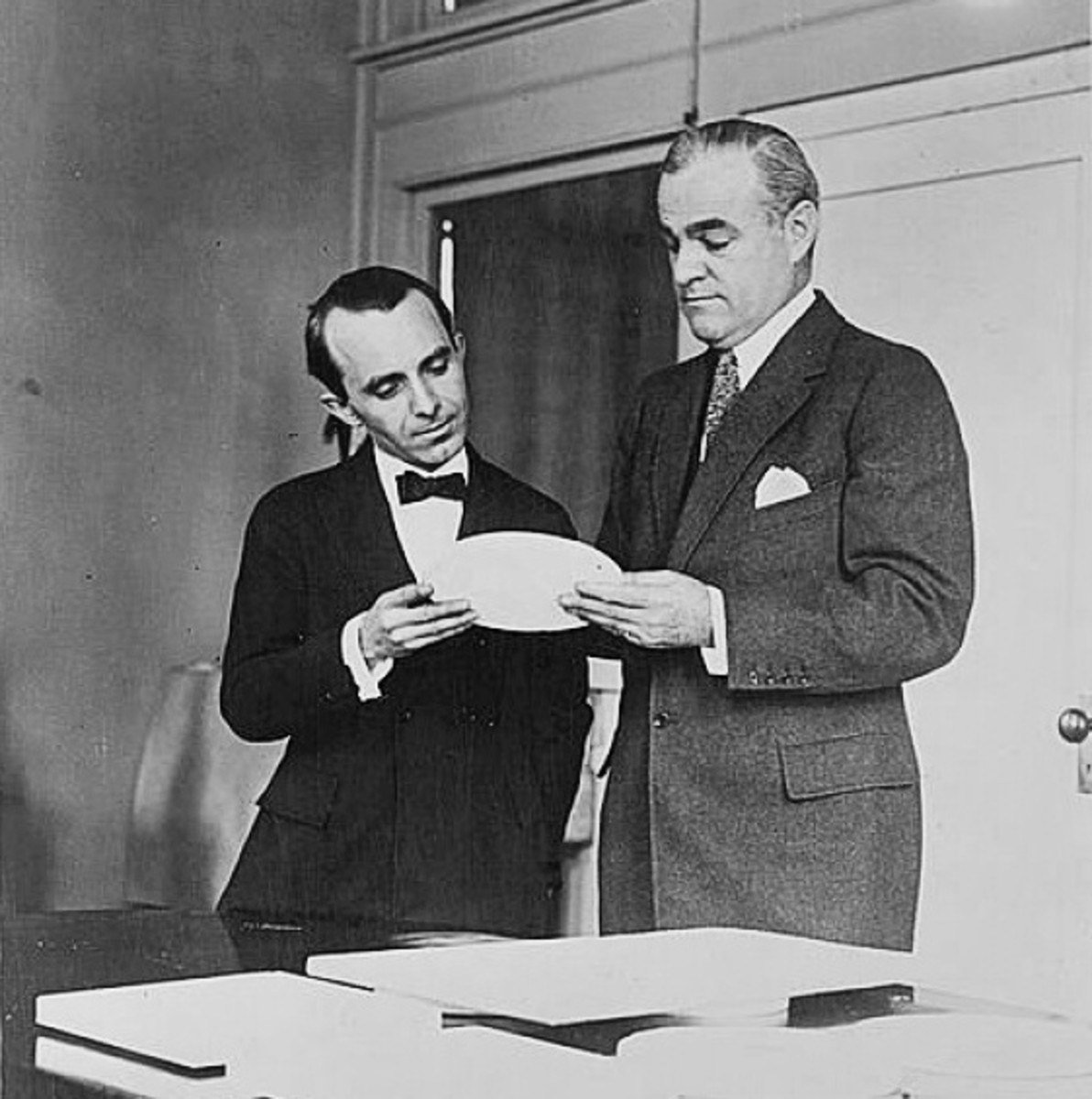 Sculptor Anthony de Francisci (left) and Mint Director Raymond T. Baker (right) inspecting a plaster model of the new silver dollar coin.