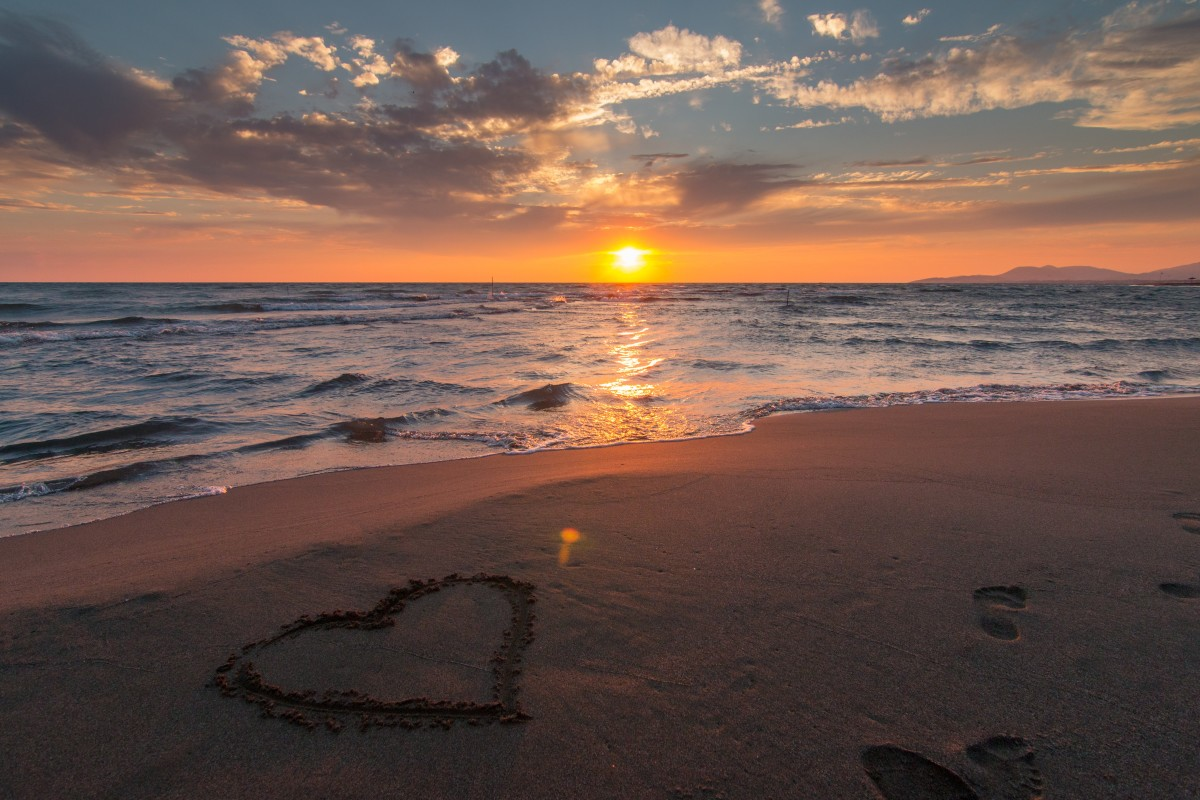 A perfect cliche setting for a romanic trip, on the beach with the sun going down.