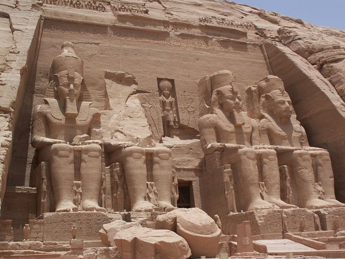 Abu Simbel temple showing large statues of Ramesses II flanked by smaller statues of his Queen Nefertari.