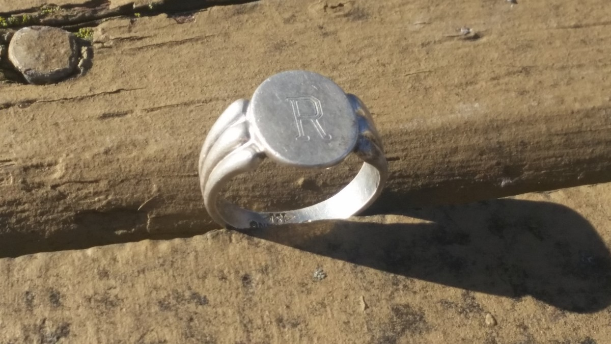 A silver initial ring I found near an old half dollar.