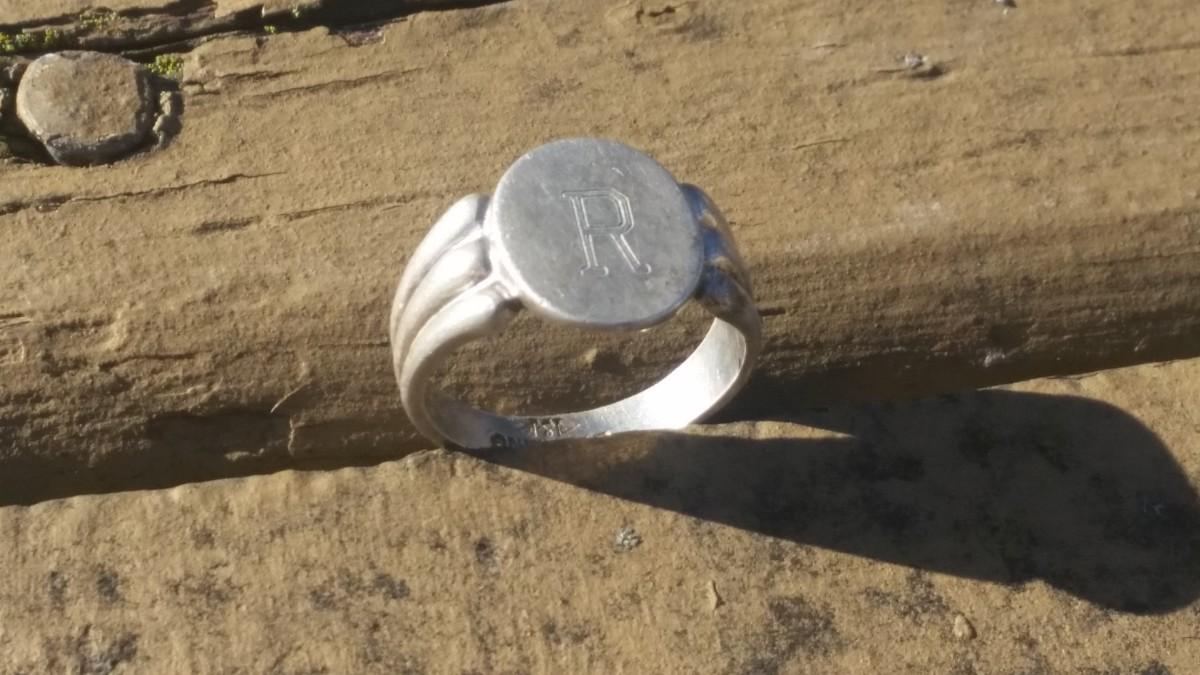 A silver initial ring I found near an old half dollar.
