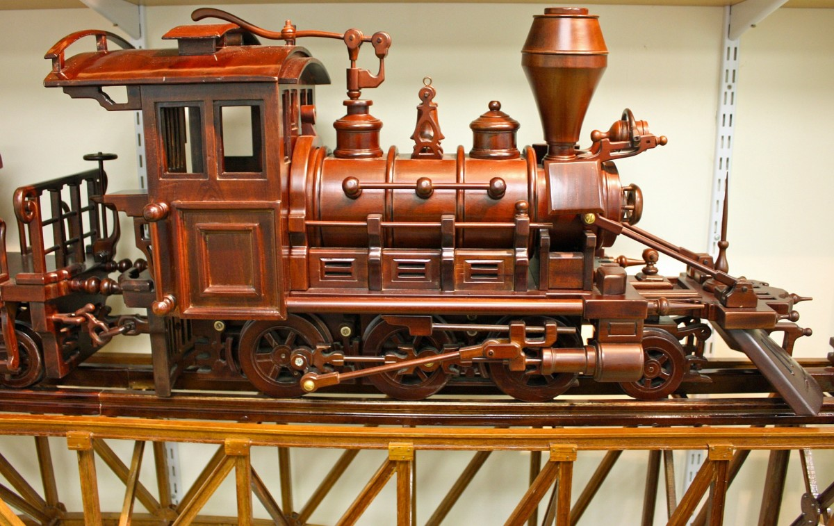 A wooden locomotive with a flat bed trailer on a wood constructed  railway track.