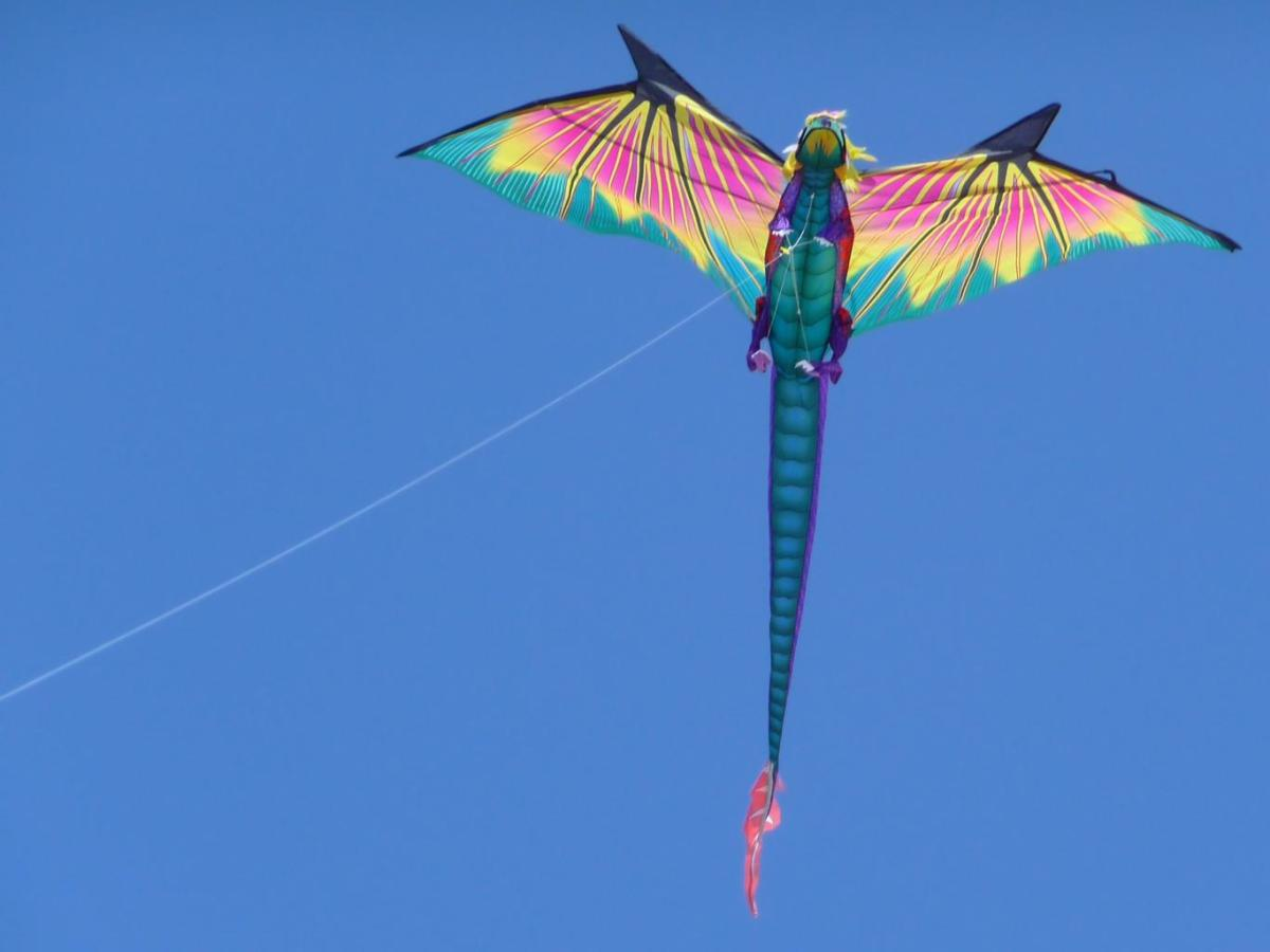 Dragon kite flying high in upright flying position.