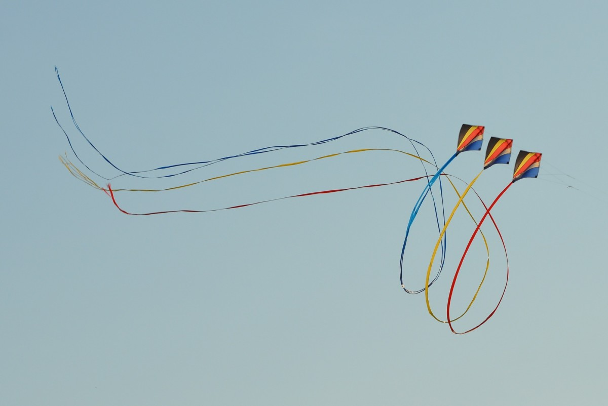 Three kites performing a ballet routine in the sky.