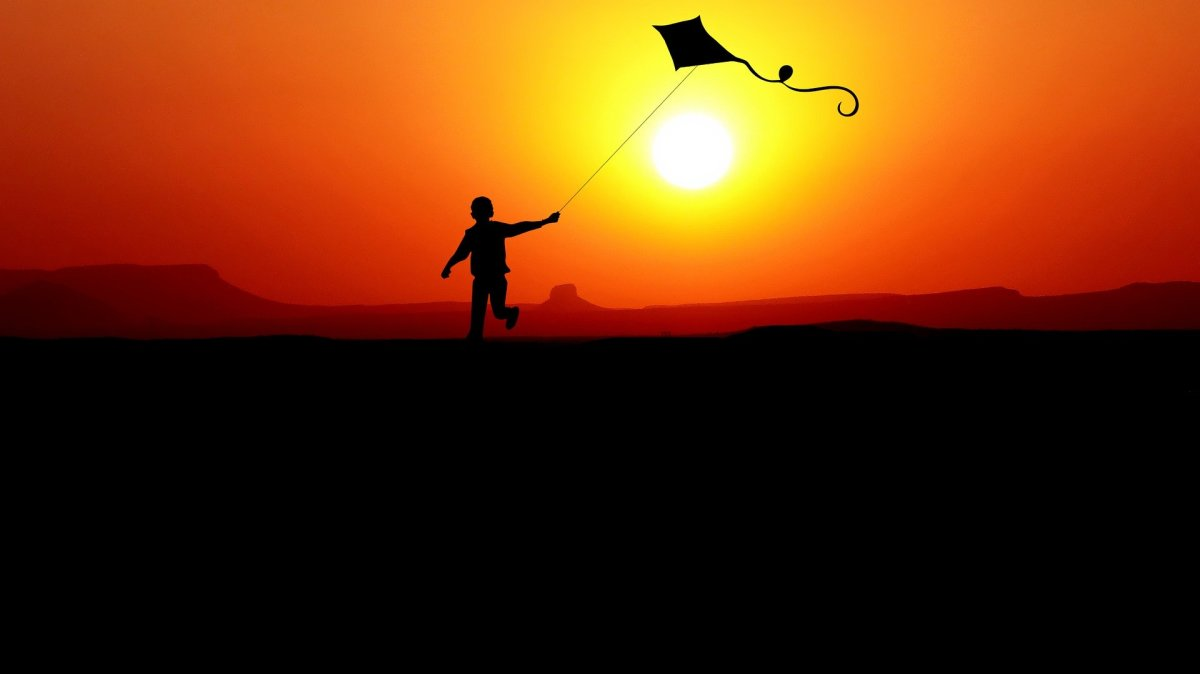 An individual flying their diamond kite during sunset.