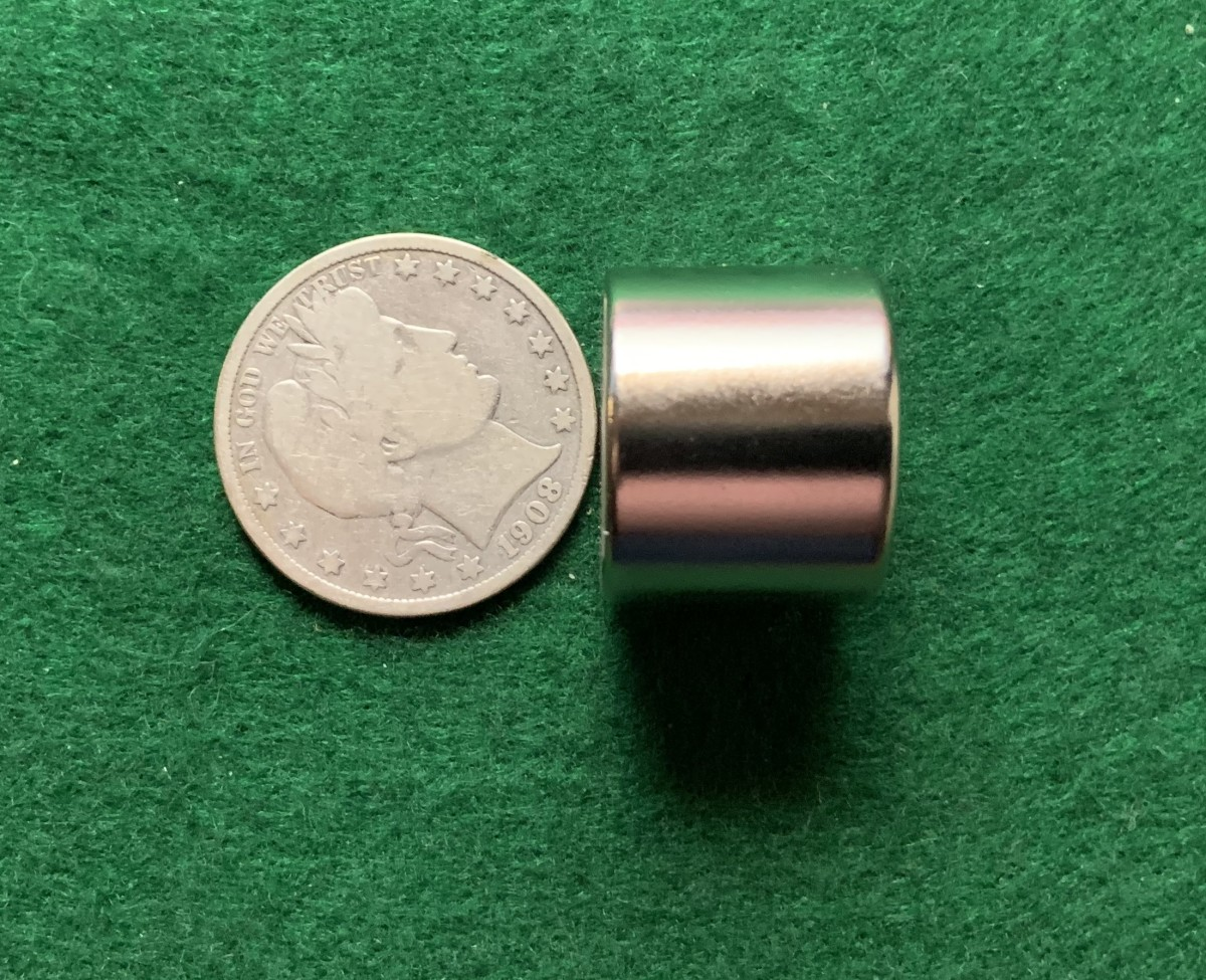 Using a strong Alnico magnet to see if a coin sticks to the magnet. This genuine silver Barber half dollar is not attracted to the magnet.