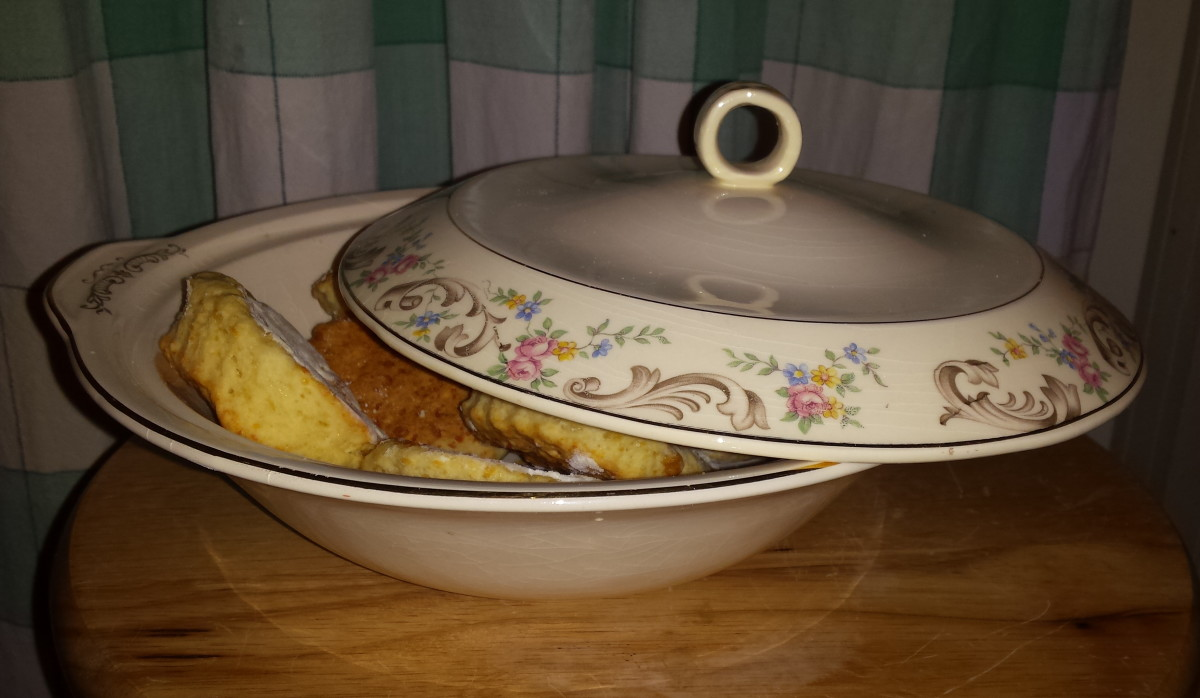 Photo of cream colored-covered porcelain serving dish with pink/blue/yellow floral pattern and gold filigree.  Dish contains biscuits/scones.