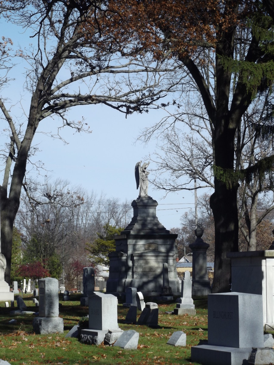 Photograph of old cemetery with large mausoleum in background featuring angel on top.  Evergreen Cemetery, Muskegon, MI.