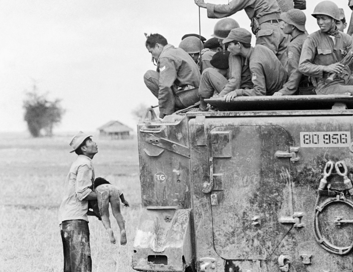 A distraught father holds the body of his child as South Vietnamese Rangers look down from their armored vehicle, March 19, 1964. The child was killed as government forces pursued guerrillas into a village near the Cambodian border.