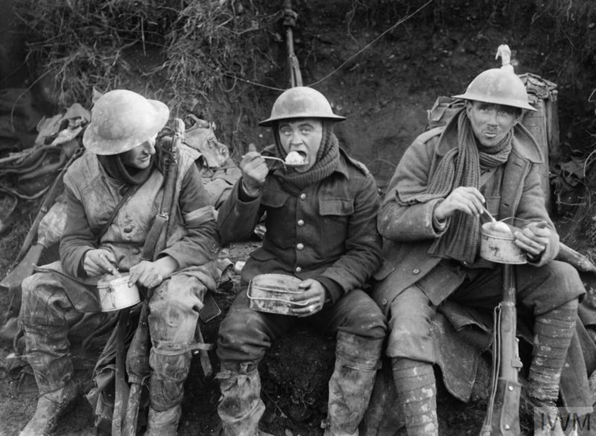 Mud-caked British soldiers enjoy a meal away from the front line during the Battle of the Somme in October 1916.