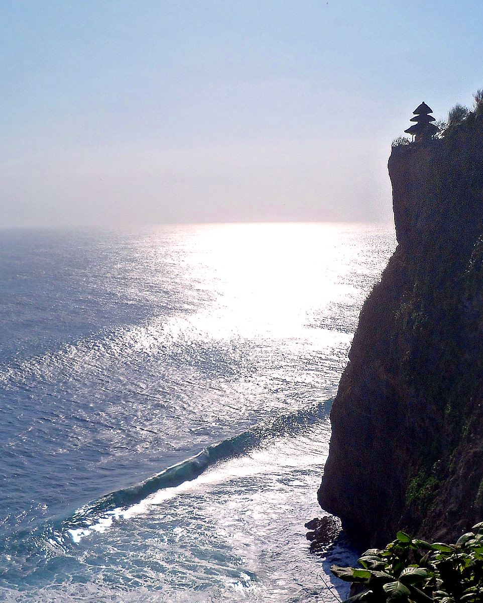 Silhouette of Uluwatu Temple against a shimmering Indian Ocean.