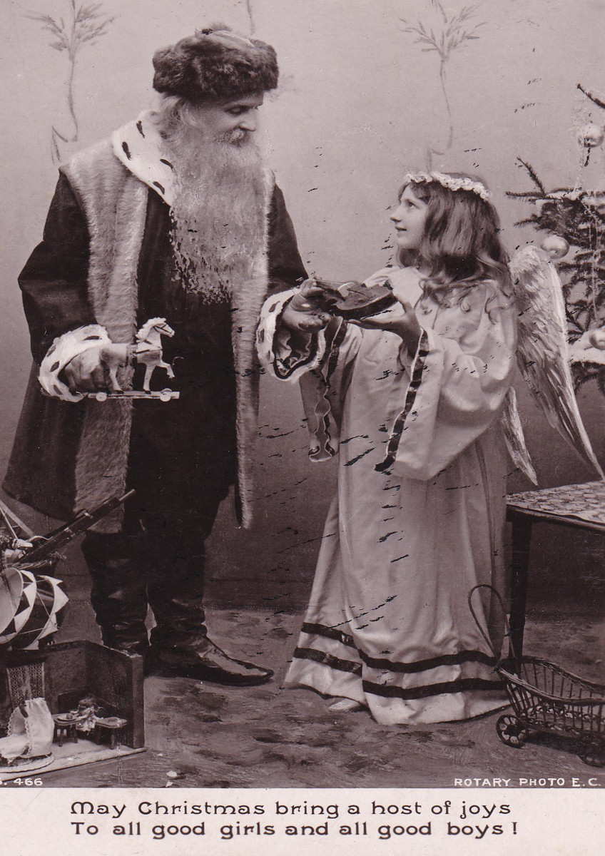 Santa Claus discusses Christmas present choices with an angel in this 1907 postcard. He already has the long white beard we are familiar with today.