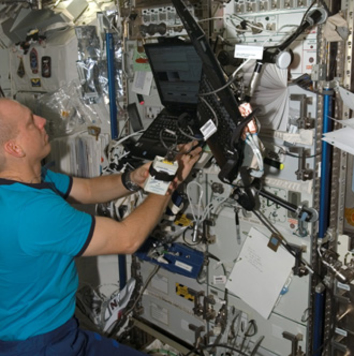 Expedition 15 Flight Engineer Clay Anderson works with a Continuous Blood Pressure Device (CBPD) and computer.