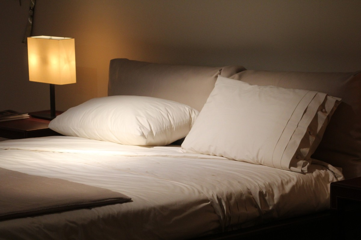 double bed with white sheets and dim lamp