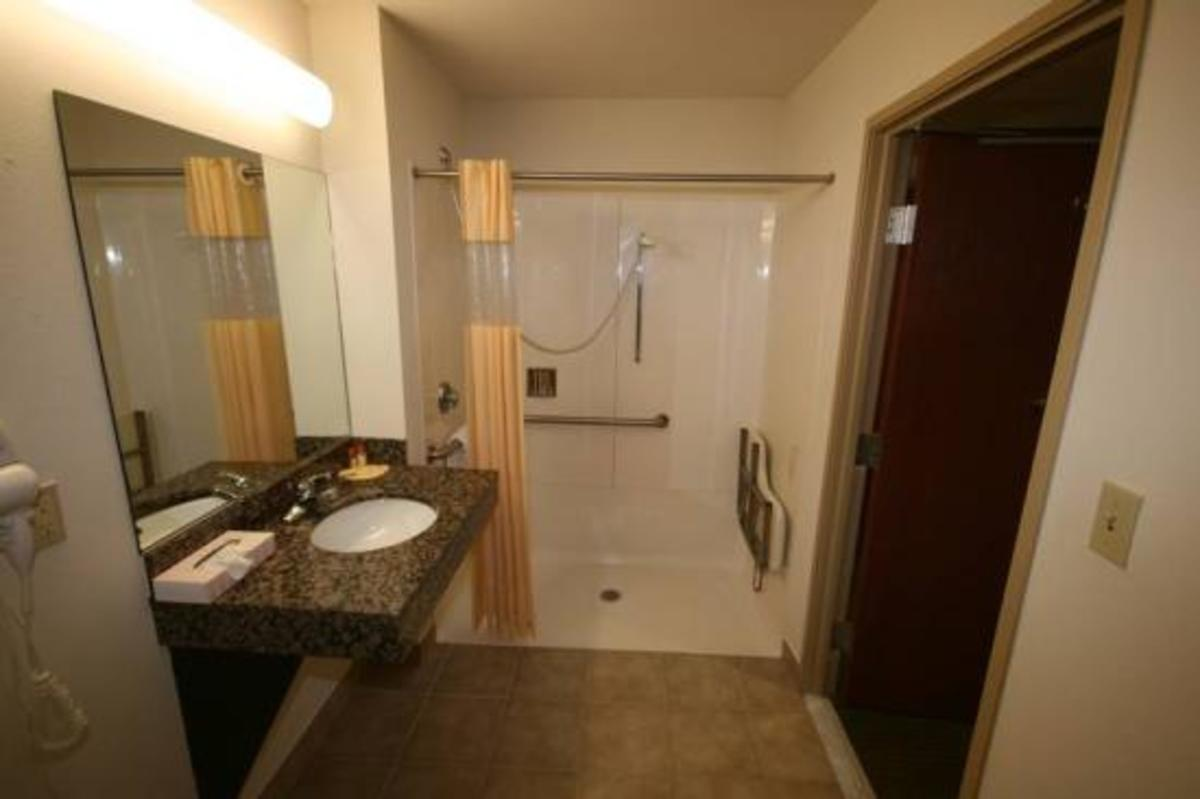Bathroom with handicap walk-in shower, safety grab bar, and shower seat.