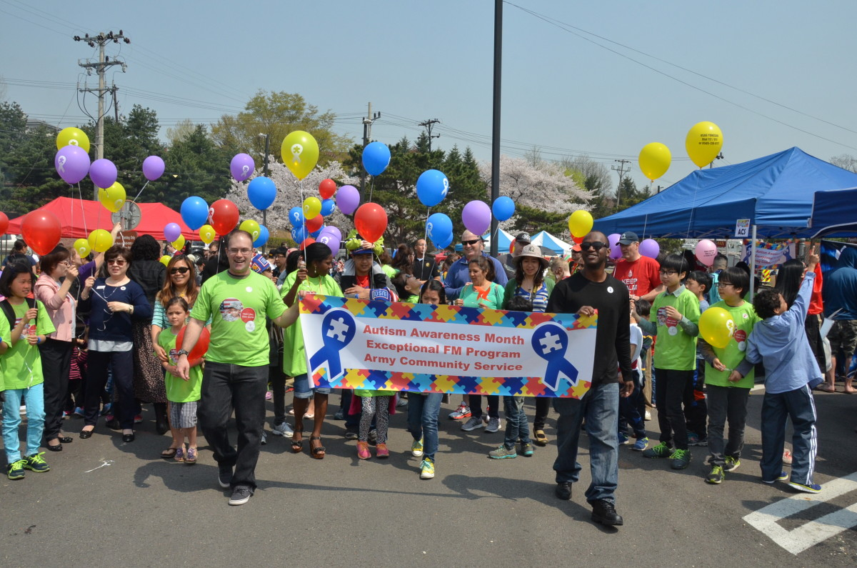 Community members march during the Autism Walk at the Fun Fair on Yongsan Garrison, April 11, 2019. Army Community Service members and volunteers pass out Autism Awareness balloons for everyone to hold.
