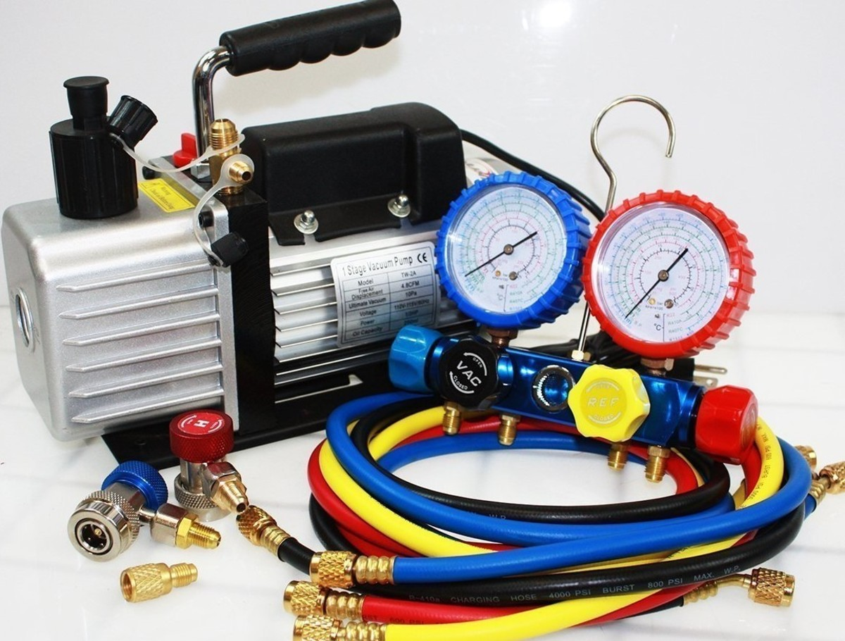 Typical portable HVAC vacuum pump with manifold gauges, hoses, and quick disconnect couplers for high/low fittings
