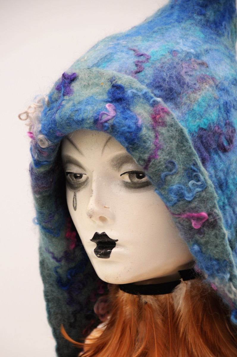 A wet-felted pixie hat with dyed Teesdale curls added to the surface for texture.