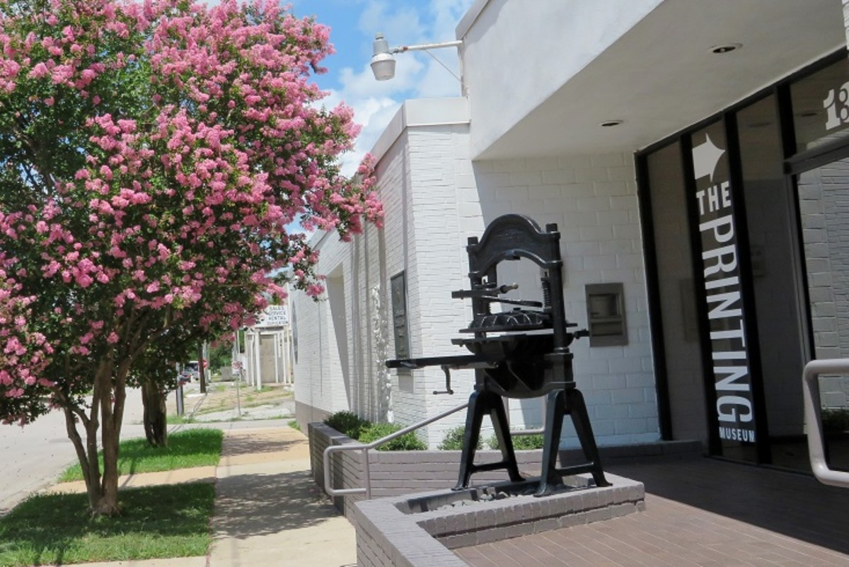Exterior of The Printing Museum with crape myrtle in bloom.