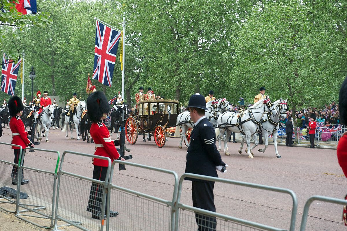 The Queen of England arrives by carriage at a royal wedding