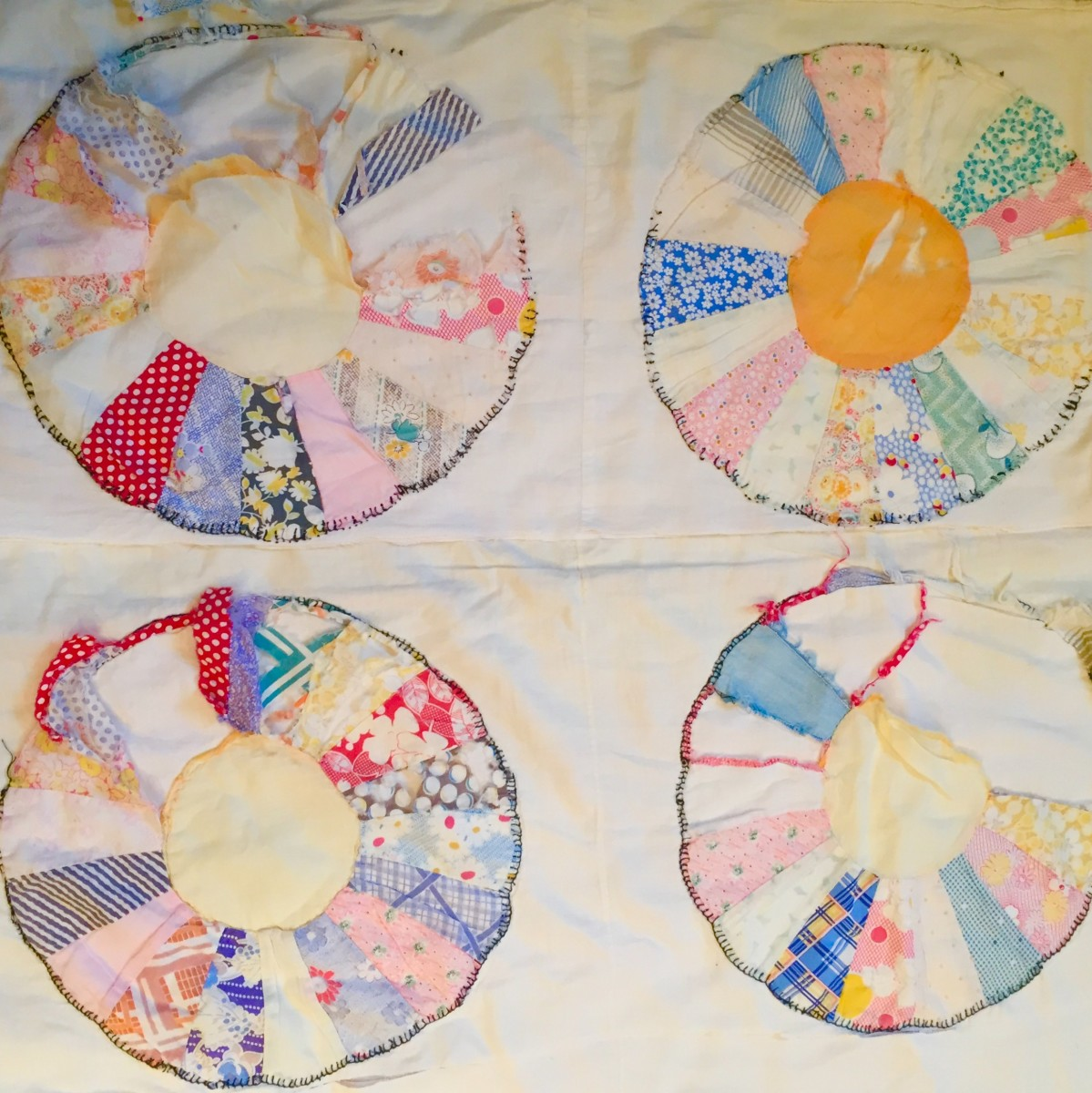 Tattered and torn blocks of the Dresden Plate Quilt Grandma made decades ago.