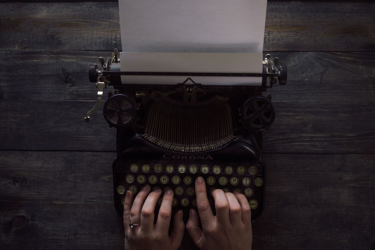 Person typing on an old-fashioned typewriter. Photo by Patrick Fore on Unsplash.